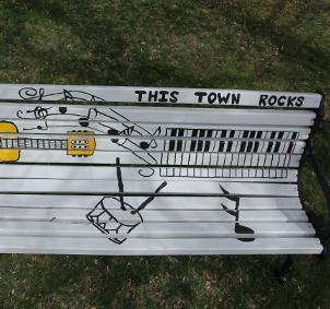 Bemalte Parkbank mit Noten, Gitarre und Drums unter dem Titel This Town rocks